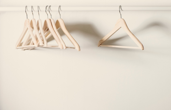 Empty hangers on a clothes rack in deserted cloakroom